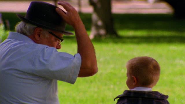 REAR VIEW MS senior man talking to + putting hat on boy outdoors