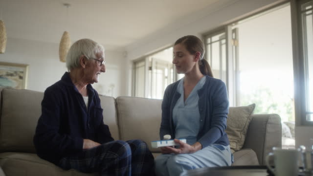 senior man talking with caregiver at home - personale sanitario video stock e b–roll