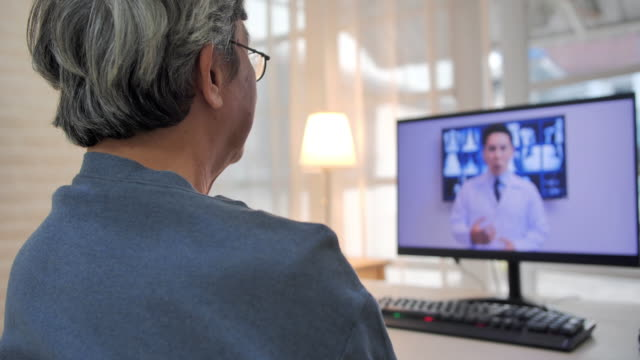 senior man talking with doctors discussing treatment plan of patient while having video conference.older man talking to his doctor via video chat.senior technology,lifestyle,people,global,retirement,video conference,medical education,medical consultation. - medical x ray stock videos & royalty-free footage
