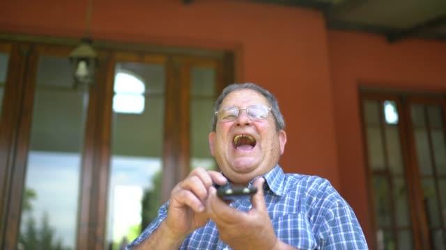 vídeos de stock e filmes b-roll de senior man talking with his mobile phone at home - 70 anos