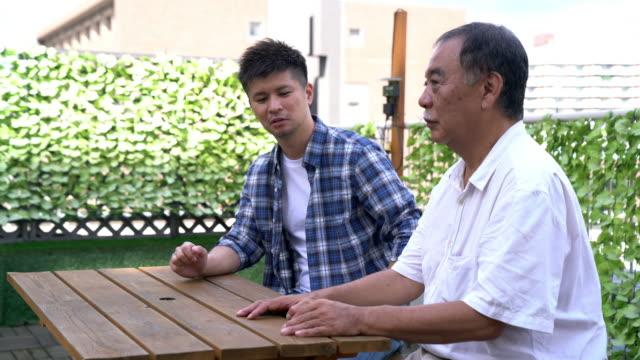 年配の男性が屋外に息子と話して - 談笑する点の映像素材/bロール