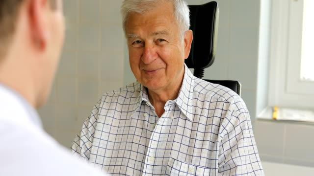 ältere mann im gespräch mit hno-arzt in klinik - männer über 40 stock-videos und b-roll-filmmaterial
