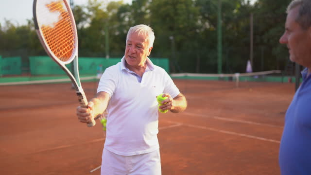 Senior man teaching his friend new tennis moves on tennis court