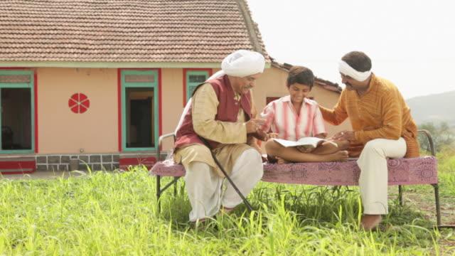senior man teaching to his grandson  - dhoti video stock e b–roll