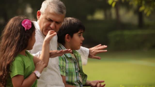 senior man telling story to his grandchildren  - großeltern stock-videos und b-roll-filmmaterial