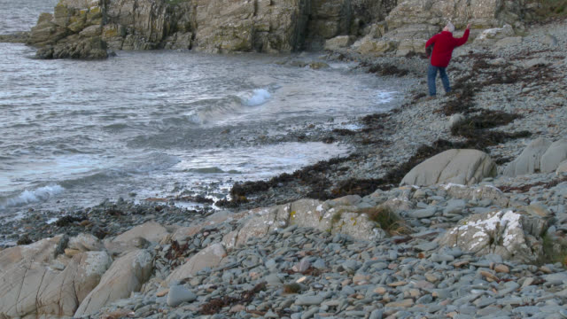 senior man throwing a stone from a rocky shore - johnfscott stock videos & royalty-free footage