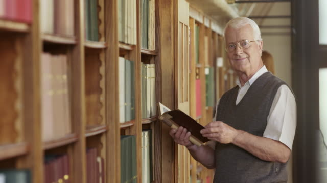 tu senior man thumbing through a book in the library - reading glasses stock videos & royalty-free footage