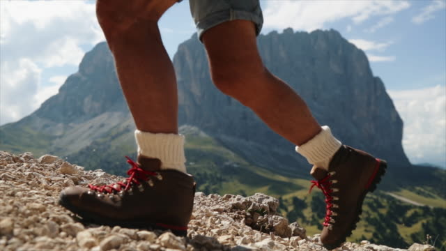Senior man trail hiking on the Dolomites: boots close up