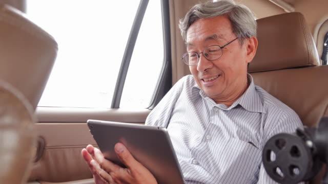 vídeos y material grabado en eventos de stock de hombre mayor viajando en taxi y mirando la tableta digital. hombre mayor tomando un taxi desde un aeropuerto y cargando la bolsa de equipaje de mano al coche. movimiento, tecnología, viaje, viaje, global, conexión, estilo de vida, vacaciones, negocios co - asiento de atrás