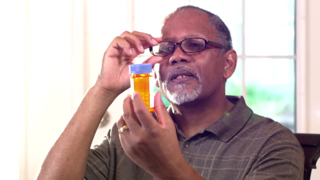 senior man trying to read prescription bottle label - prescription medicine home stock videos & royalty-free footage