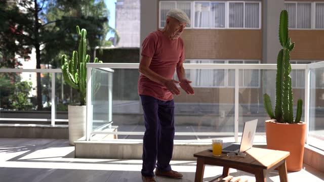 vidéos et rushes de un homme âgé qui allume un ordinateur portable commence à faire de l'exercice à la maison - seniornaute