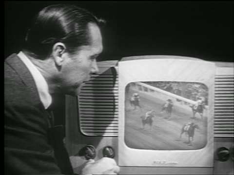 b/w 1948 senior man turns knob + watches horse race on television + smiles - 1948 stock-videos und b-roll-filmmaterial