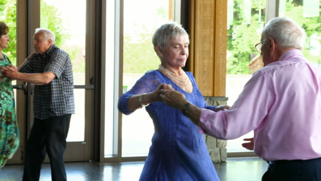 TS Senior man twirling wife while dancing in community center