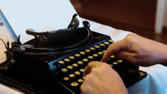 年配の男性が 4 k で古いタイプライターの入力