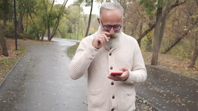 senior  man uses a smartphone. one person - grey hair stock videos & royalty-free footage