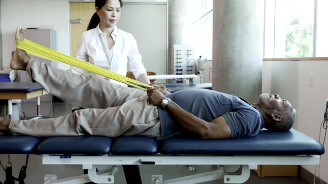 senior man uses resistance band during physical therapy session - film tilt stock videos & royalty-free footage