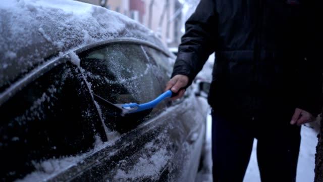 vídeos y material grabado en eventos de stock de senior hombre utilizando una escoba para limpiar su coche - abrigo de invierno