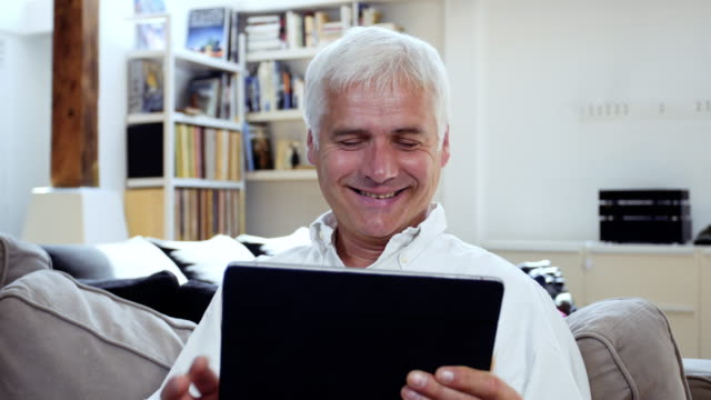 vídeos de stock, filmes e b-roll de senior man using a digital tablet - idoso na internet