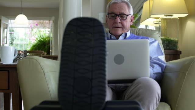 senior man using a laptop at home with his broken leg propped up - broken leg stock videos & royalty-free footage