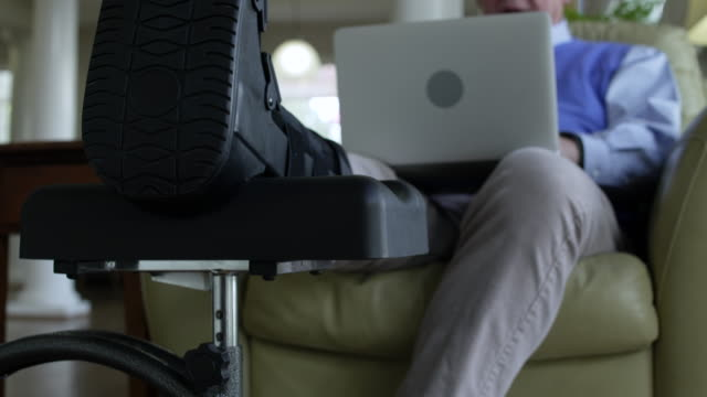 senior man using a laptop at home with his broken leg propped up - piedi alzati video stock e b–roll