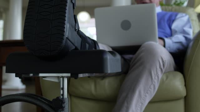 vídeos de stock, filmes e b-roll de senior man using a laptop at home with his broken leg propped up - de pé para cima