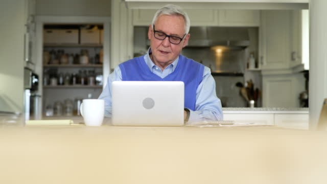 Senior man using a laptop in a dining room