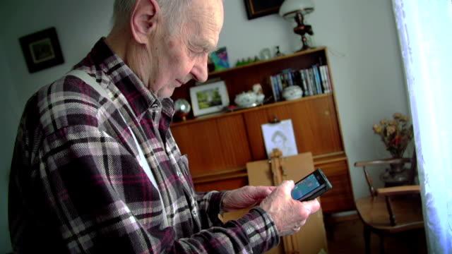 vídeos de stock e filmes b-roll de homem idoso a utilizar um telemóvel ou telefone inteligente - 70 anos