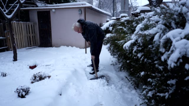 senior man using a snow shovel in a front yard - spade stock videos & royalty-free footage