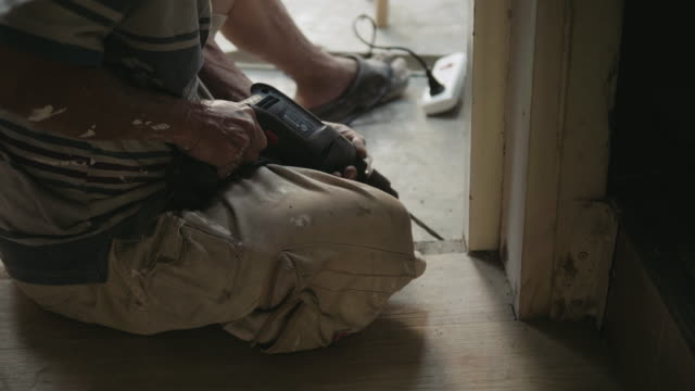 Senior man using an electric drill for DIY at home.