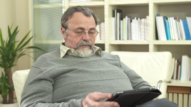 hd :dolly 老人男性デジタルタブレットを使用して、 - 片付いた部屋点の映像素材/bロール