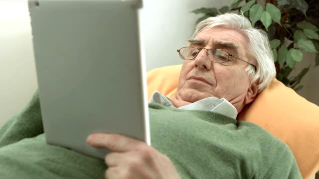 hd :老人男性デジタルタブレットを使用して、 - 片付いた部屋点の映像素材/bロール