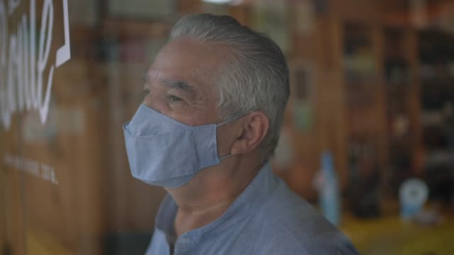 senior man using face mask looking through window on his small business - working seniors stock videos & royalty-free footage