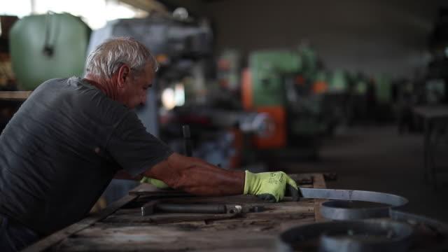 stockvideo's en b-roll-footage met senior man met hamer voor het buigen van metaal in de fabriek - ijzer