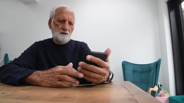 vidéos et rushes de senior man using his mobile phone at home - seniornaute