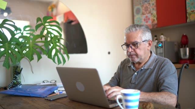 vídeos de stock, filmes e b-roll de idoso usando laptop em casa - e commerce
