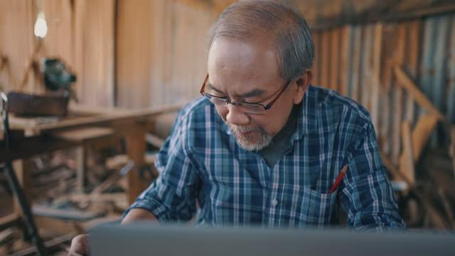 vidéos et rushes de homme aîné utilisant l'ordinateur portatif pour vérifier la commande du client - étude de marché