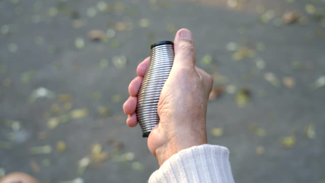 senior man using metal stress relief for exercise hand and finger - donne anziane video stock e b–roll