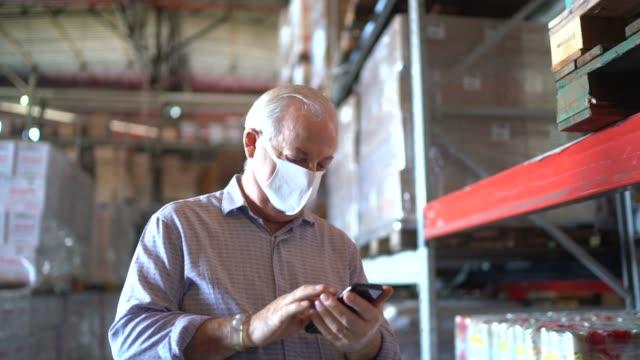 senior-mann mit handy im lager - mit gesichtsmaske - employee engagement stock-videos und b-roll-filmmaterial