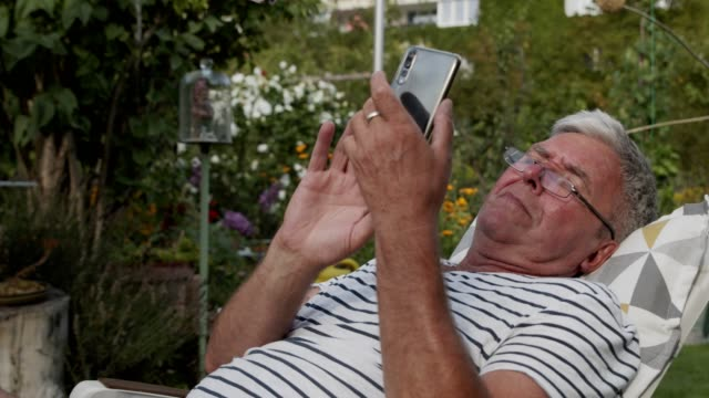 senior man using mobile phone, holding smart phone, texting, surfing internet - reading glasses stock videos & royalty-free footage