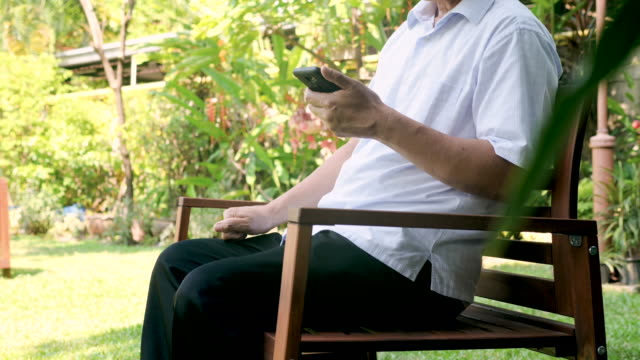 senior man using mobile phone in the park. - lost stock videos & royalty-free footage