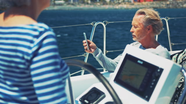senior man using phone while woman steering yacht - yacht stock videos & royalty-free footage