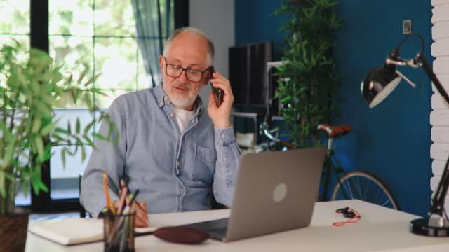 vidéos et rushes de homme aîné utilisant le téléphone tout en travaillant sur l'ordinateur portatif au bureau à la maison - 60 64 ans