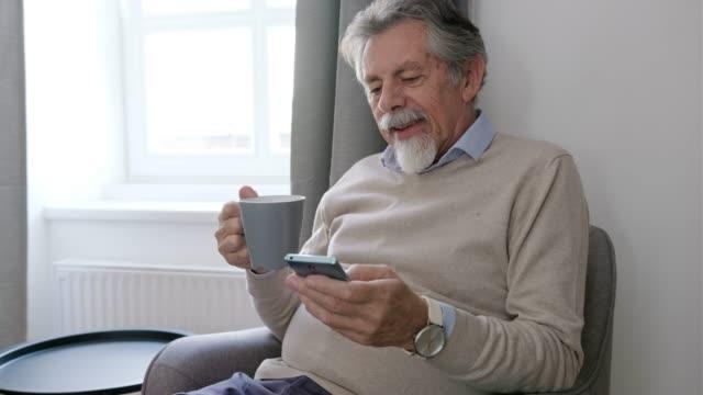 senior man using smart phone and drinking coffee - slovenia stock videos & royalty-free footage