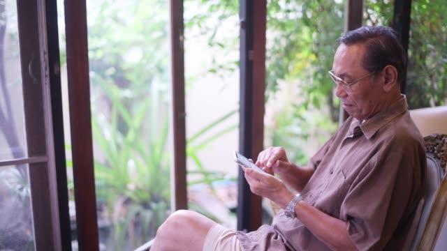 senior man använder smart telefon - följa rörlig aktivitet bildbanksvideor och videomaterial från bakom kulisserna