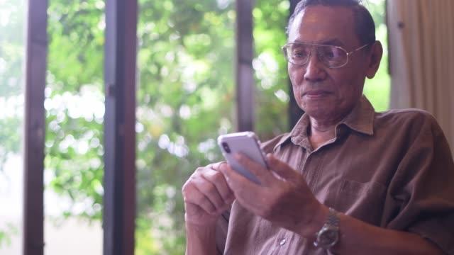 seniorenmann mit smartphone - großvater stock-videos und b-roll-filmmaterial