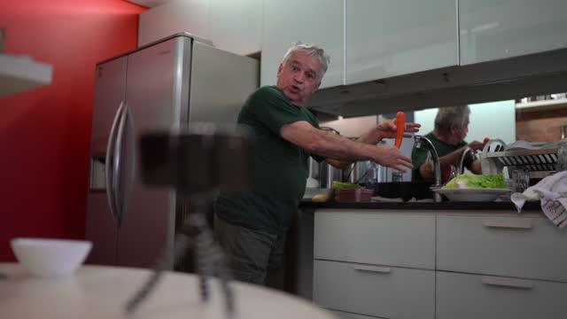 vídeos de stock, filmes e b-roll de idoso usando smartphone em um tripé para gravar vídeo ensinando como cozinhar vegetais - preparação