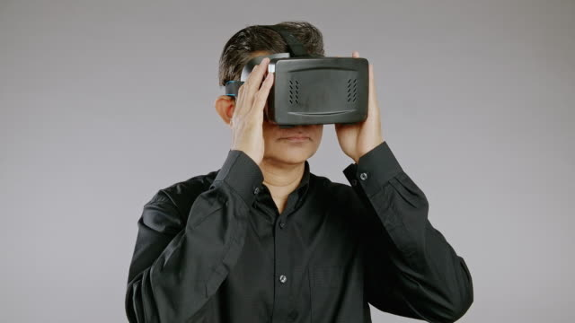 senior man using virtual reality headset, looking around, isolated in grey background. asian man in black shirt. - black shirt stock videos & royalty-free footage