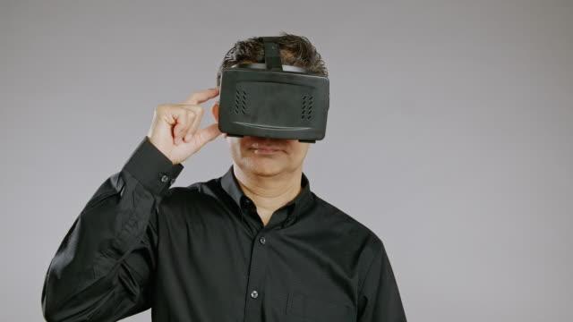 senior mann mit virtual-reality-headset, schalten sie es ein, lächeln, isoliert in grauen hintergrund. asiatischer mann im schwarzen hemd. - schwarzes hemd stock-videos und b-roll-filmmaterial