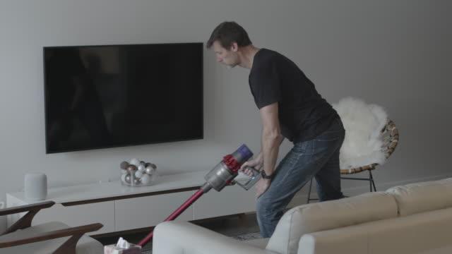 リビングルームを掃除機をかけるシニアマン - 掃除機点の映像素材/bロール
