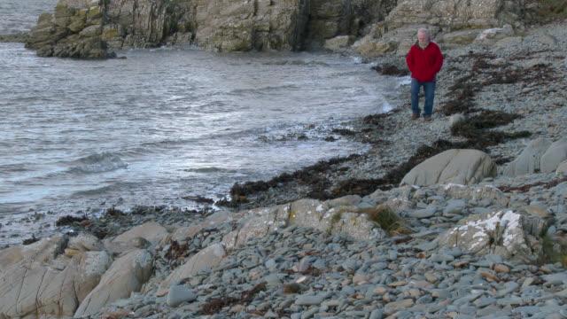 äldre man går längs en rocky shore - johnfscott bildbanksvideor och videomaterial från bakom kulisserna